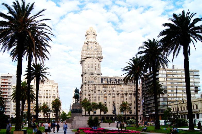 Der Plaza Independencia in Montevideo ist von imposanten Gebaeuden, Palmen und Statue umgeben